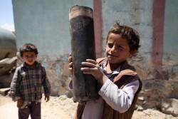 首都サヌアの近郊にある村で、爆発した砲弾の残骸を手にする男の子。