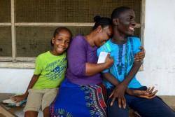 接触者たちが身を寄せる経過観察のための一時ケアセンターから出てきた子どもたちを抱きしめる、子どもたちの母親の友人。