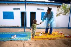 防護服に身を包んだスタッフと遊ぶ、母親をエボラで亡くした1歳6カ月の子ども。ウィルスの潜伏期間である21日の間隔離され、ユニセフが支援する保育施設の敷地内で過ごす。