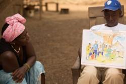 フォレカリアのコミュニティで、エボラに関する知識を紙芝居で伝えるコミュニティスタッフ。