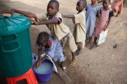 教室に入る前に消毒用の塩素が入った水で手を洗う子どもたちの列。