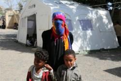 ユニセフのテントの仮設教室の前に立つワジーダさんと甥っ子たち。
