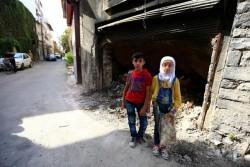 荒廃した建物の近くに立つホムス旧市街出身の12歳の双子。(シリア)