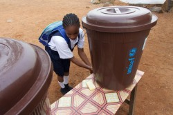 教室に入る前に消毒用の塩素が入った水で手を洗う女の子(リベリア)