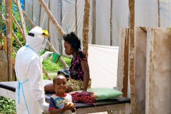In July 2014 in Sierra Leone, a health worker, wearing head-to-toe protective gear, offers water to a woman with Ebola virus disease (EVD), at a treatment centre for infected persons in Kenema Government Hospital, in the city of Kenema, Eastern Province. A young boy stands nearby. Workers in the treatment centre are stretched to capacity. UNICEF is supporting the hospital by providing treatment supplies like intravenous fluids and equipment such as protective gear and body bags. As of 4 August, a total of 1,711 cases, including 932 deaths, had been attributed to EVD in the four West African countries of Guinea, Liberia, Nigeria and Sierra Leone. Sierra Leone has borne 691 of these cases (576 confirmed, 49 probable and 66 suspected), including 286 deaths.