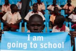 「再び学ぼう」キャンペーンの支援を受けたジュバの生徒たち。「僕は学校に通うんだ」と書かれたバナーを掲げる男の子。