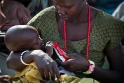 すぐ口にすることのできる栄養治療食を与える母親。