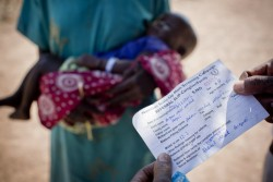 栄養不良の子どもの照会状を読む、栄養不良児の治療ケアを行うセンターの保健員。
