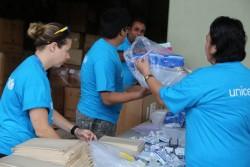 首都スバにあるユニセフの倉庫で支援物資の水と衛生キットや学校用の物資を詰めるユニセフのスタッフとボランティア。