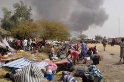 避難施設が全焼し、マラカルの文民保護区内の道路に避難する子どもたちや家族。