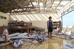 サイクロンの被害に遭い、瓦礫や本が散乱する学校の図書館にたたずむ高校生の少女。