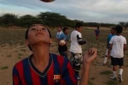 ユニセフのロゴが入ったFCバルセロナのユニフォームを着てサッカーをする男の子。