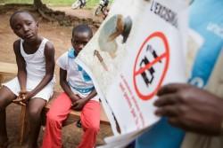 FGM/Cに関するコミュニティの集会で、啓発活動のポスターを見る子どもたち。(コートジボワール)