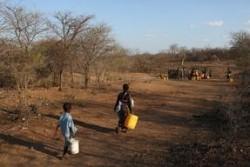 水を汲みに歩く母子