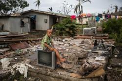 サイクロンで破壊された自宅に残されたテレビの上に座る7歳の男の子。