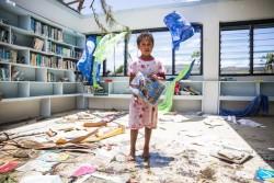 サイクロンの被害にあった小学校の図書館で本を手にたたずむ女の子。