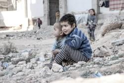 アレッポにある国内避難民が身を寄せる避難所の近くの道で座っていた3歳と4歳の男の子。