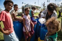 フィジー政府によって届けられた水を給水タンクに汲む人々。