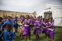 ユニセフが提供する仮設教室用テントで授業が再開され、笑顔を見せる子どもたち。