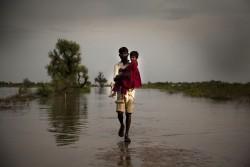 洪水が一面に広がり、娘を抱いて水没した道を歩く父親(パキスタン、2011年)
