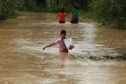 荷物を抱えて台風で洪水が起こった村の中を歩く少年。(フィリピン)