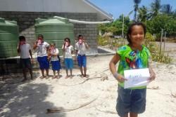 新しく設置された雨水貯水備蓄施設で安全な飲み水を手にすることができるようになったキリバスの子どもたち。「水は、飲み物」と書かれた紙を手に笑顔を見せる少女。