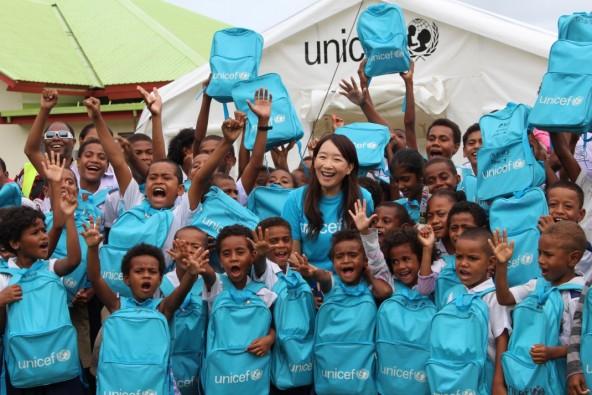 オバラウ島ロレト小学校 ユニセフの支援で設置されたテント造りの仮設教室の前で、子どもたちと。 ユニセフは、学用品がセットになったスクールバッグも配布した。