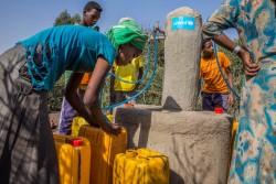 ユニセフが設置支援した給水所でタンクに水を汲む女性。