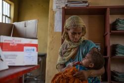 すぐ口にすることができる栄養補助食を2歳の息子に食べさせる母親。