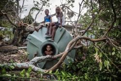 サイクロン・ウィンストンで倒れた給水タンクで遊ぶ子どもたち。