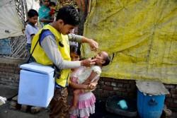 戸別訪問を行い、ポリオの予防接種を行う保健員。(インド)