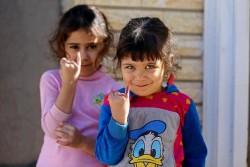 """ポリオの予防接種を受けた小指に付けられた紫色の""""しるし""""を見せる子どもたち。(イラク)"""