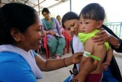 上腕部を測り、栄養状態の検査を受ける子ども。