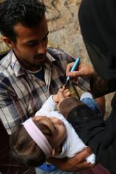 """ポリオの予防接種を受けた""""しるし""""を赤ちゃんの小指に付ける保健員。(シリア)"""