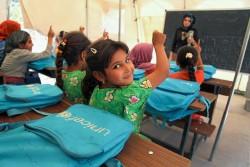 テントの教室で先生の質問に手を挙げて答える子どもたち。(イラク)