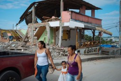 地震の被害にあった建物の前を、女性二人に手を引かれて歩く少女。