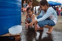 水で手を洗う避難所に身を寄せる女の子たち。