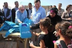 ヨルダンのザータリ難民キャンプに新設された学校でユニセフの支援物資を子どもたちに手渡すユニセフ事務局長。