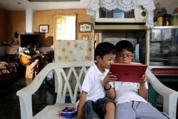 タブレットでインターネットを使う男の子たち。(フィリピン)
