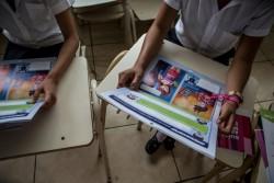 インターネット上のリスクや性的搾取から身を守るための啓発資料を読む子どもたち。(エルサルバドル)