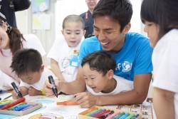 子どもたちと一緒にチーム旗作りをする長谷部選手。