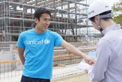 建設工事の関係者から、新園舎の完成予定図とともに説明を受ける長谷部選手。