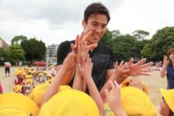 熊本市立健軍小学校の子どもたちとハイタッチする長谷部選手。
