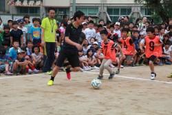 熊本の子どもたちと一緒にサッカーをする長谷部選手。