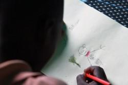 ボコ・ハラムに村が襲われたときのことを絵に描く男の子。(ニジェール)