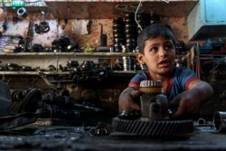 バグダッドで父親の仕事を手伝う6歳の男の子。