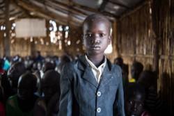 ベンティウの文民保護地区の学校に通う5歳の男の子。毎日、母親のお古の小さな腰掛を最前列に持ち込み先生に近い席を確保する。200人もの生徒が1つの教室で学ぶ日もある。