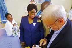 「マム・コネクト」と呼ばれる携帯電話のSMSを活用したプロジェクトを試すレーク事務局長。「マム・コネクト」は、HIVと共に生きる妊婦に向けて、病院への検診のリマインドを送信する(南アフリカ)
