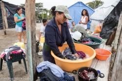 非公式の避難場所に身を寄せ、指定された場所で子どもや孫らと一緒に洗濯をする女性。湿度が高いこの地域では太陽が出ている日中に洗濯を乾かすことに努めている(2016年7月、ラチョレラ)