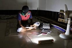 薄暗い部屋の中で、試験勉強のために本を読むアーメッドさん。(イエメン南部アデン州クレーター地区)